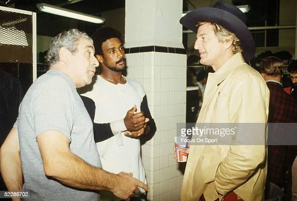 Boston Red Sox's Jim rice listens to teammate Ken Harrelson talk in a cowboy hat inside the players locker room circa 19671969