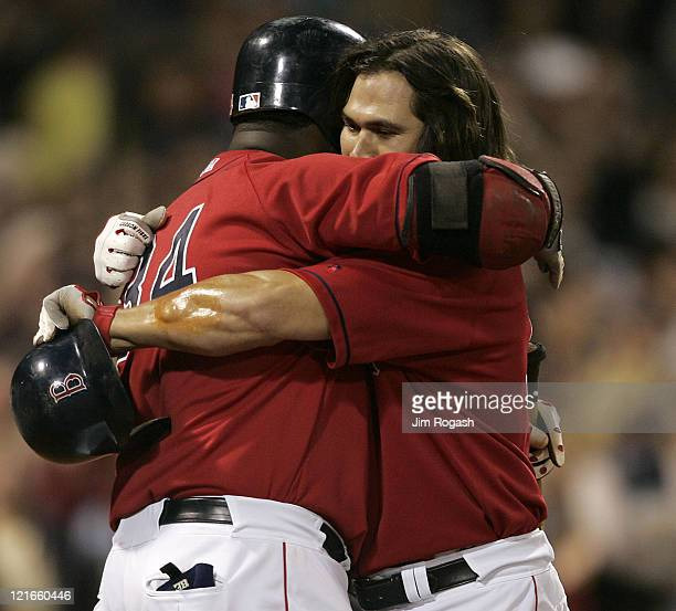 Boston Red Sox's Johnny Damon right is hugged by teammate David Ortiz after Damon hit ahome run against the New York Yankees at Fenway Park in Boston...
