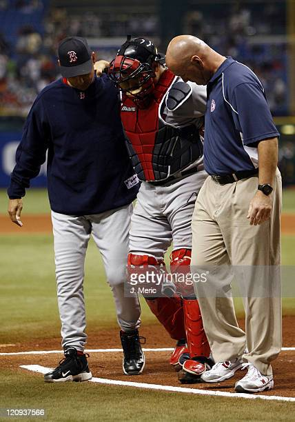 Boston starting catcher Doug Mirabelli is helped off the field by manager Terry Francona and head trainer Paul Lessard during Friday night's game...