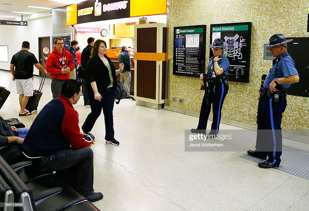 Boston State Police stand guard in the baggage claim area of Logan International Airport on April 16, 2013 in Boston, Massachusetts. Security is tight in the Boston following yesterday's two bomb explosions at the finish of the Boston Marathon, which killed three people and injured at least 176 others.