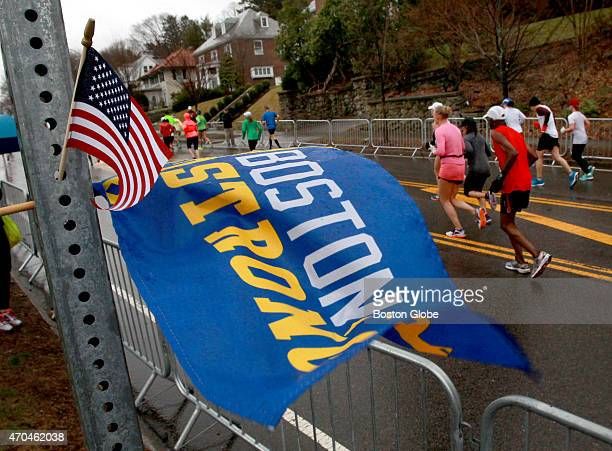 Boston Strong flag flaps in the same headwind facing runners on Commonwealth Avenue as they climb Heartbreak Hill in Newton Mass during the Boston...