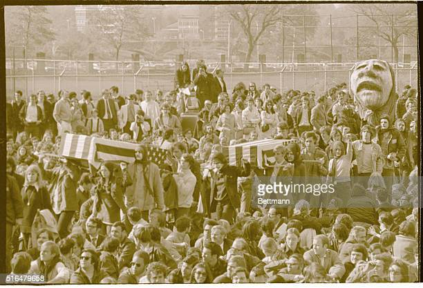 Students carry mock caskets through crowd as some 50000 persons gathered near Harvard Stadium May 8 to listen to speeches against the expanded...