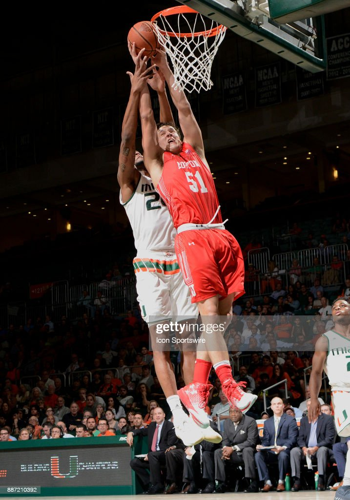 Boston U forward Max Mahoney (51) and Miami forward Dewan Huell (20) reach for a rebound during a college basketball game between the Boston University Terriers and the University of Miami Hurricanes on December 5, 2017 at the Watsco Center, Coral Gables, Florida. Miami defeated Boston U