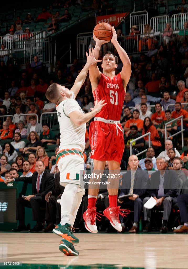 Boston U forward Max Mahoney (51) shoots against Miami guard Dejan Vasiljevic (1) during a college basketball game between the Boston University Terriers and the University of Miami Hurricanes on December 5, 2017 at the Watsco Center, Coral Gables, Florida. Miami defeated Boston U