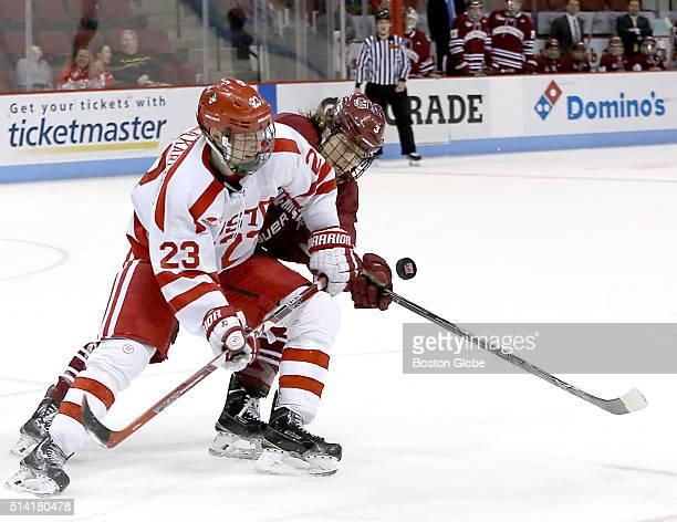 Boston University forward Jakob ForsbackaKarlsson battles with UMass Amherst defenseman Callum Fryer for control of the puck during third period...