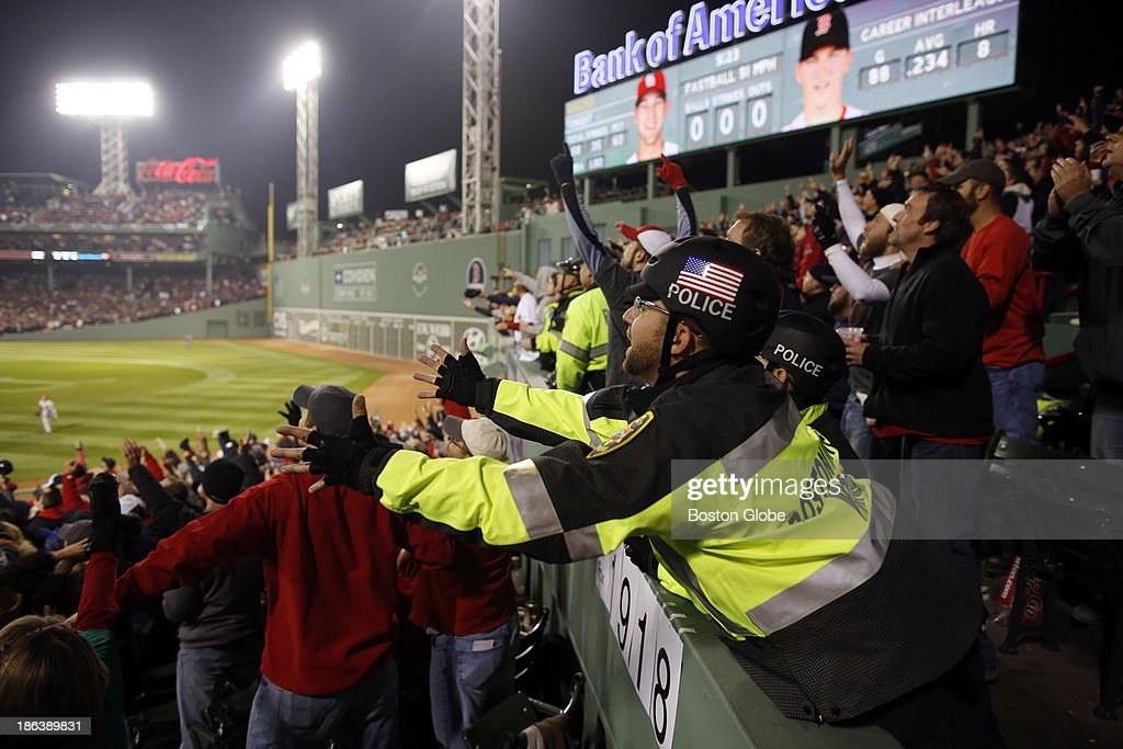 A Boston University Police officer reaches out to catch a Red Sox home run during the fourth inning. The Boston Red Sox host the St. Louis Cardinals at Fenway Park for Game Six of the 2013 Major League Baseball World Series, Oct. 30, 2013.