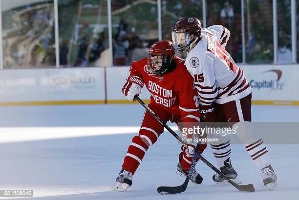 Boston University Terriers forward Tommy Kelley and UMass Minutemen forward Ray Pigozzi battle for position on a face off during a Frozen Fenway NCAA...