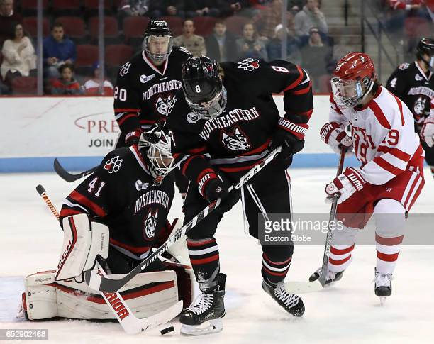 Boston University's Kieffer Bellows puts pressure on Northeastern University goalie Ryan Ruck as Adam Gaudette clears the puck during the first...