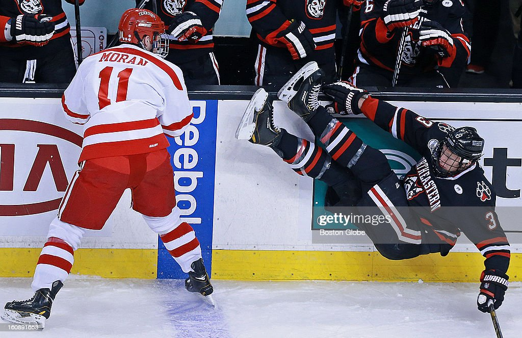 Boston University's Mike Moran, left, sent Northeastern's Josh Manson, right, crashing to the ice with a first period check in front of the Husky's bench. Northeastern University met Boston University in the early game of the annual Beanpot Hockey Tournament at the TD Garden.