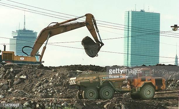 Boston's Big Dig construction on the Central Artery tunnel continues as dirt is piled up against skyline showing the Prudential and John Hancock...