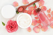 with pink rose petals. Jar of body moisturizer, attar bottle toning lotion, top view homemade cosmetic ingredients.