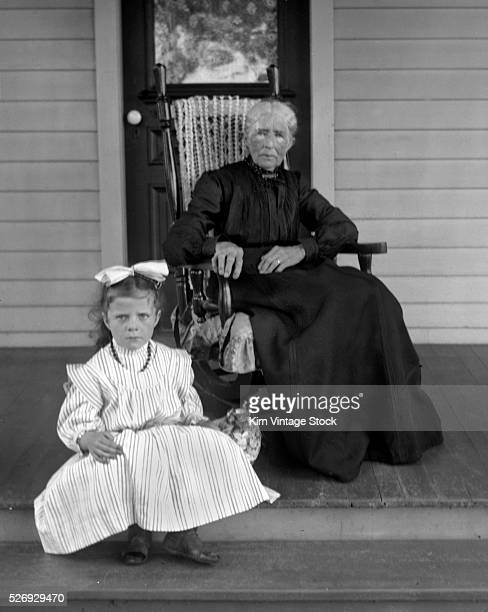 Both grandma and grandchild have a concerned look on their face while they sit on the porch