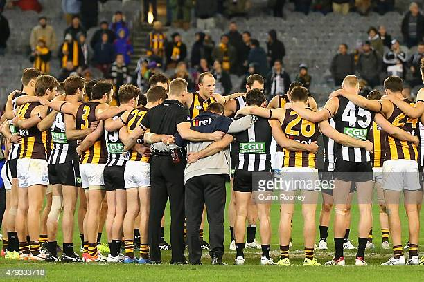 Both sides huddled together in the middle of the ground after the game to pay respect to Phil Walsh during the round 14 AFL match between the...