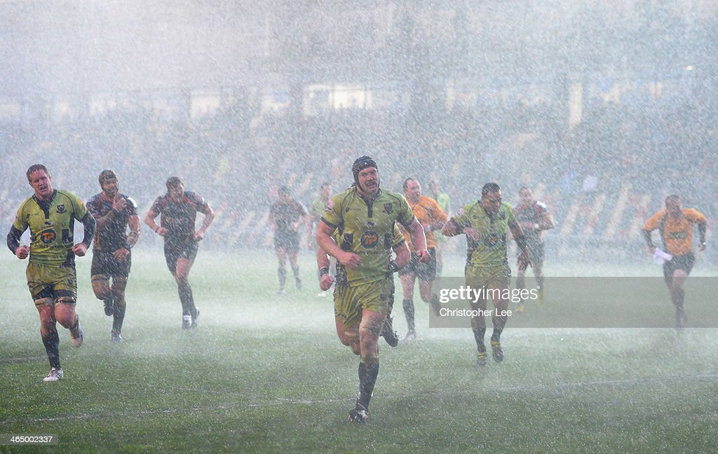 Both teams run into the changing rooms as the match is abandoned for 5 mins due to a heavy hail storm during the LV Cup match between Newport Gwent...