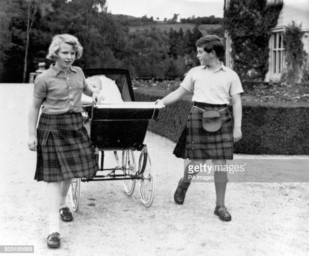 Both wearing a kilt 10 year old Princess Anne and 11 year old Prince Charles share the task of pulling the pram of baby brother Prince Andrew for a...