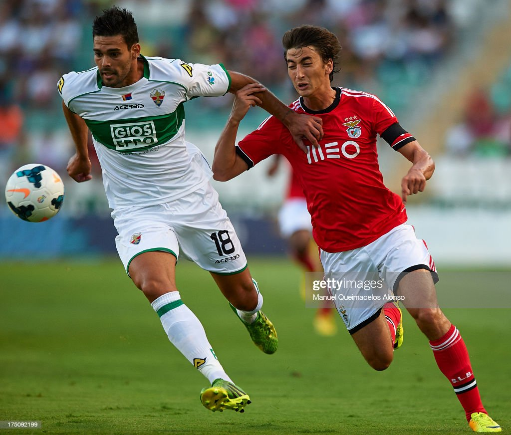 Botia (L) of Elche competes for the ball with Djuricic of Benfica during a friendly match between Elche CF and Benfica at Estadio Martinez Valero on July 31, 2013 in Elche, Spain.
