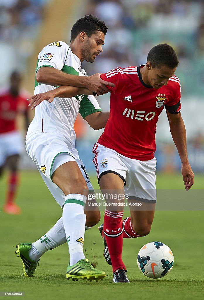 Botia (L) of Elche competes for the ball with Rodrigo of Benfica during a friendly match between Elche CF and Benfica at Estadio Martinez Valero on July 31, 2013 in Elche, Spain.