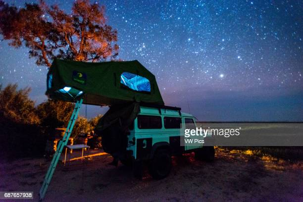Botswana Africa Land Rover parked with a pop up tent on its roof under the night sky