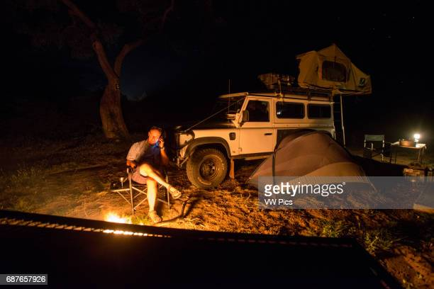 Botswana Africa Man sitting by a fire on the phone with his Land Rover in the background