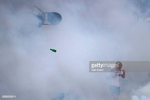 A bottle and chair are thrown as an England fan walks through tear gas as England fans clash with police in Marseille on June 10 2016 in Marseille...