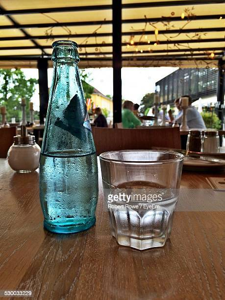 Bottle And Drinking Glass On Table At Restaurant