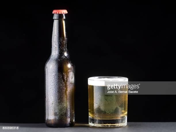 Bottle and drinking-glass  of beer with the glass esmerilado with drops of water and a steam cloud frozen on a black bottom