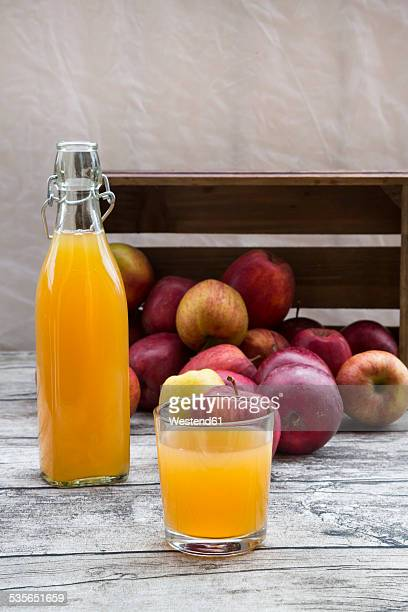 Bottle and glass of apple juice and red apples on wood