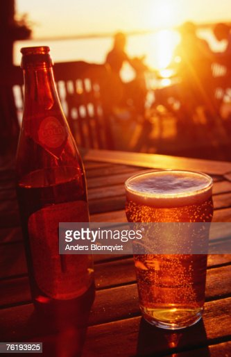 Bottle and glass of beer by Lake Vattern at sunset, Motala, Ostergotland, Sweden, Europe : Stock Photo