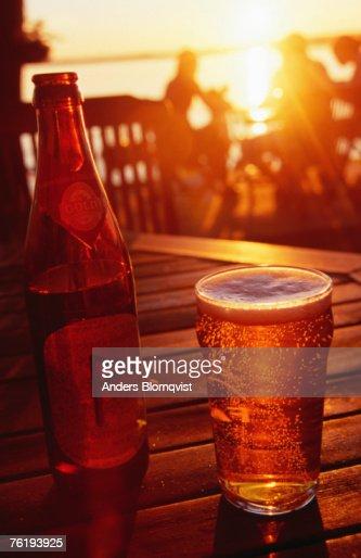 Bottle and glass of beer by Lake Vattern at sunset, Motala, Ostergotland, Sweden, Europe : Foto de stock