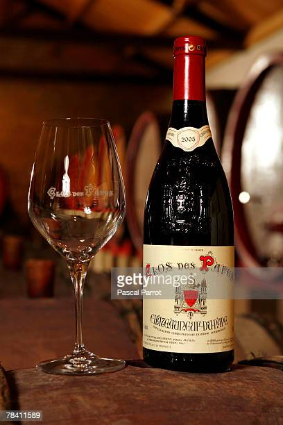 A bottle and glass of wine are displayed in the cellar of prizewinning French winegrower PaulVincent Avril on December 12 2007 in ChateaneufDuPape...