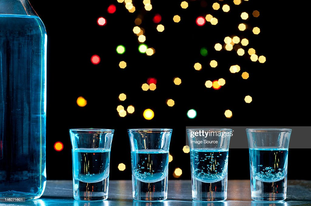 Bottle and shots of blue alcohol : Stock Photo