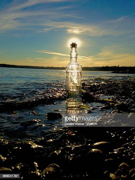 Bottle At Calm Sea Against Sunset