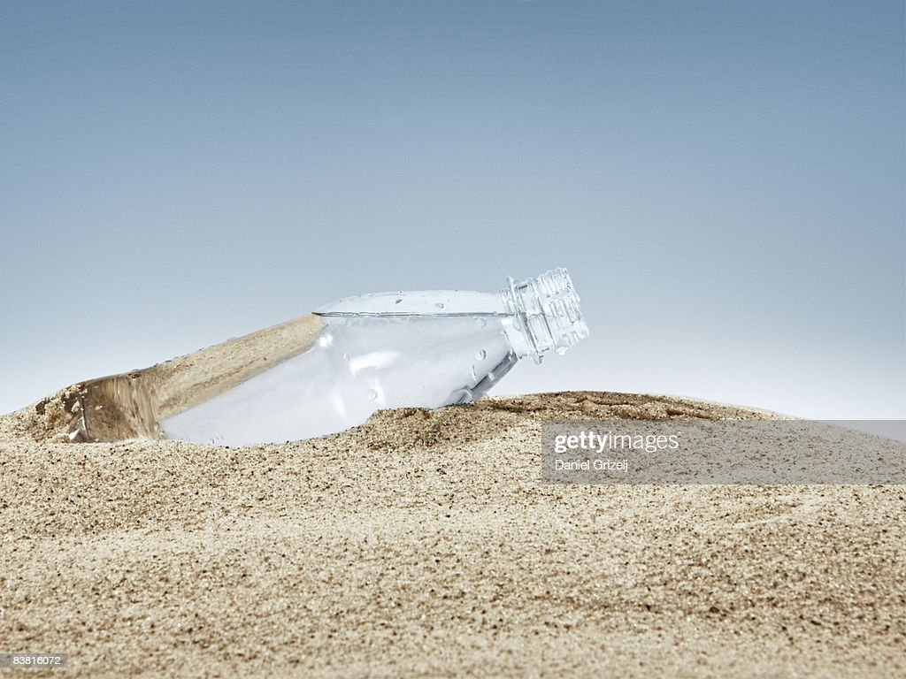bottle in sand : Stock Photo