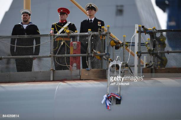 A bottle is broken on the hull of HMS Prince of Wales as Prince Charles Duke of Rothesay and Camilla Duchess of Rothesay attend a naming ceremony for...