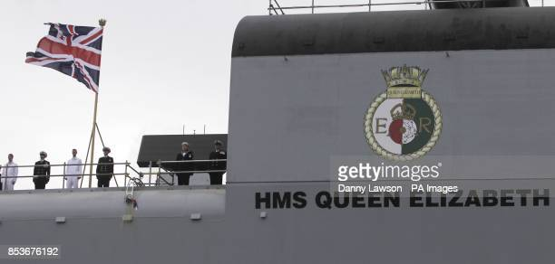 A bottle is smashed on the side of the Royal Navy's new aircraft carrier HMS Queen Elizabeth as Queen Elizabeth II officially named the ship during a...