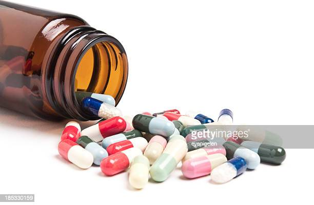A bottle laying on its side with colorful pills spilling