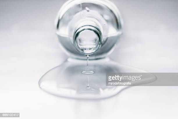Bottle lying on table with water coming out