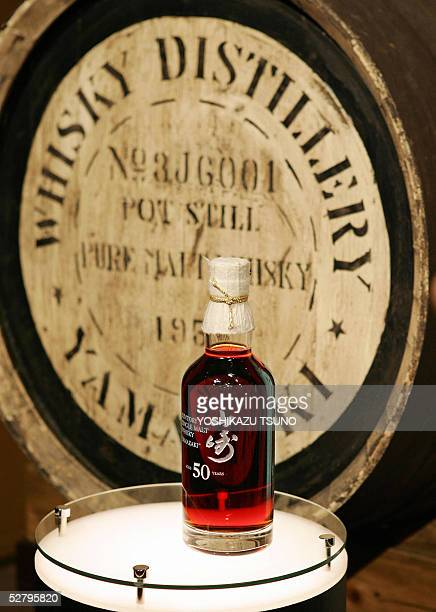A bottle of 50yearold single malt whisky is displayed before a cask barreled in 1953 as Suntory unveils Japan's most expensive whisky called...