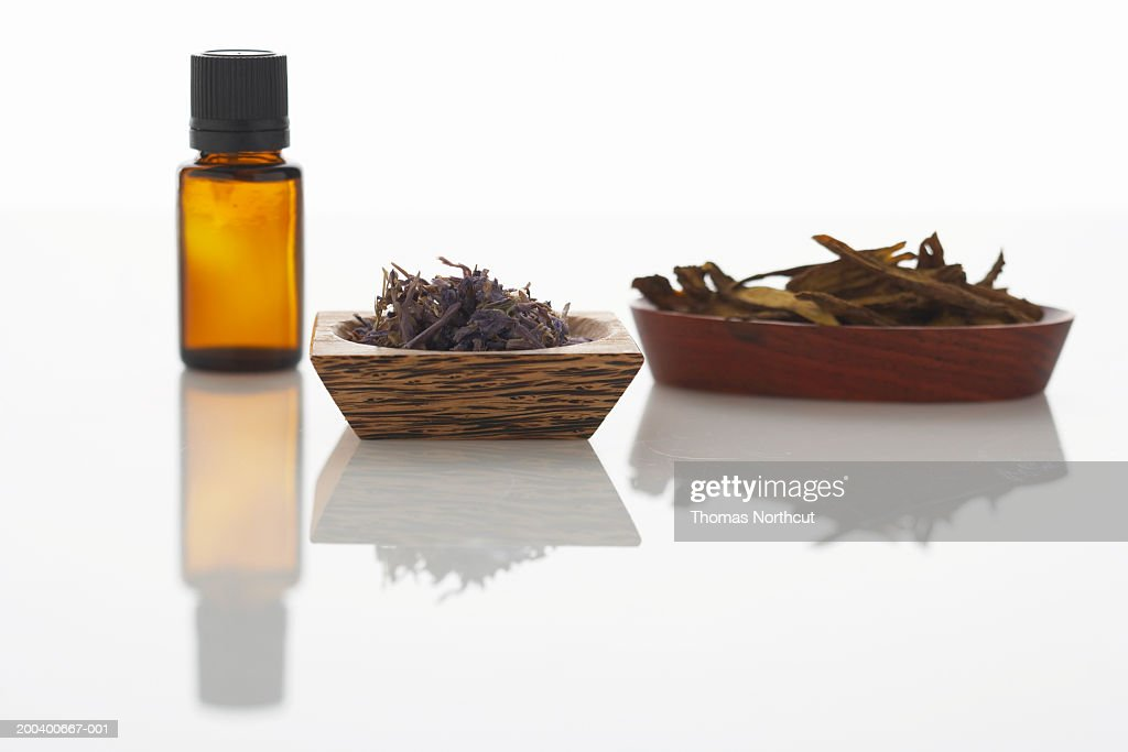 Bottle of aromatherapy oil, dried lavender and Chinese skullcap