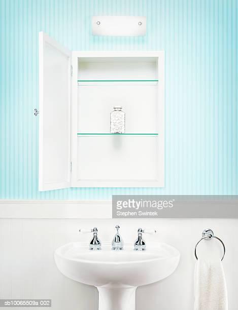 Bottle of aspirin set alone in open medicine cabinet in bathroom