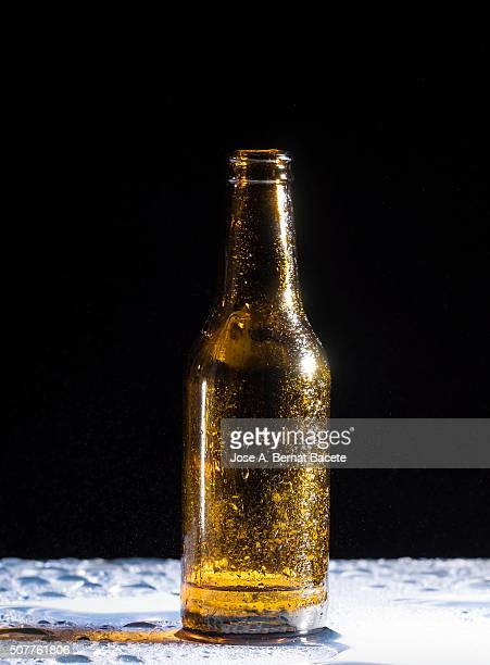 Bottle of beer empties on a table with water drops