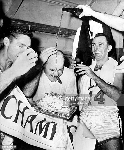 A bottle of beer is poured over Boston Celtic's coach Red Auerbach as Bill Sharman bites into a piece of victory cake and Bob Cousy smiles happily...