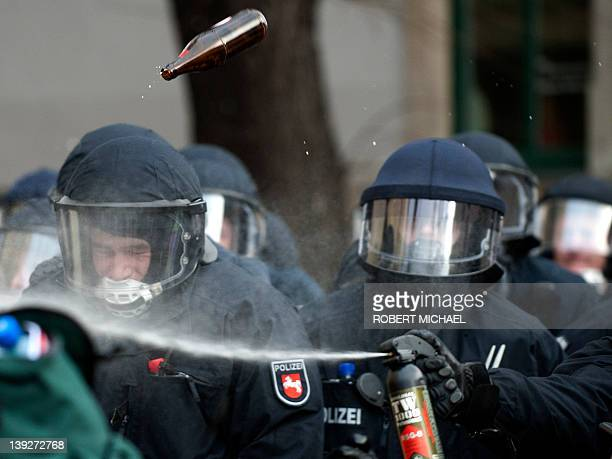 A bottle of beer is thrown at a group of police men during they use pepper spray against leftist demonstrators after a demonstration against...