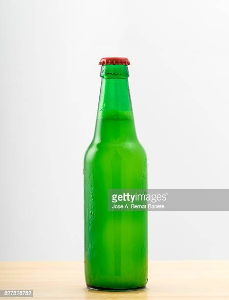 Bottle of beer with the glass esmerilado with drops of water and a steam cloud frozen on a white bottom