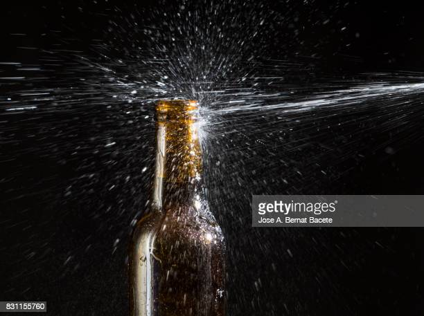 Bottle of beer with the glass esmerilado with drops of water and a steam cloud frozen on a black background