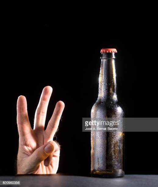 Bottle of beer with the glass esmerilado with drops of water and the hand of a man with a hand gesture of three fingers on a black bottom
