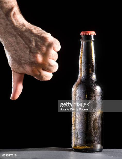 Bottle of beer with the glass esmerilado with drops of water and the hand of a man with  thumb down on a black background