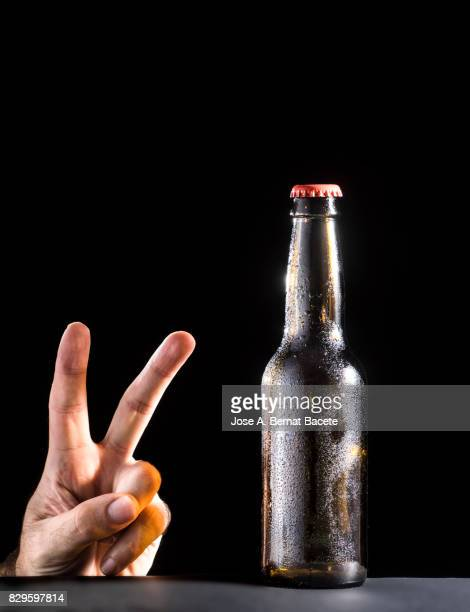 Bottle of beer with the glass frosted with drops of water and the hand of a man with a hand gesture of two fingers on a black bottom