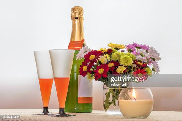 Bottle of champagne and Two filled champagne flutes on table