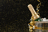Celebrating new year, birthday, xmas party. Bottle of champagne in a bucket and colorful tinsel on black backgroud with golden glitters, copy space. Mockup for postcard